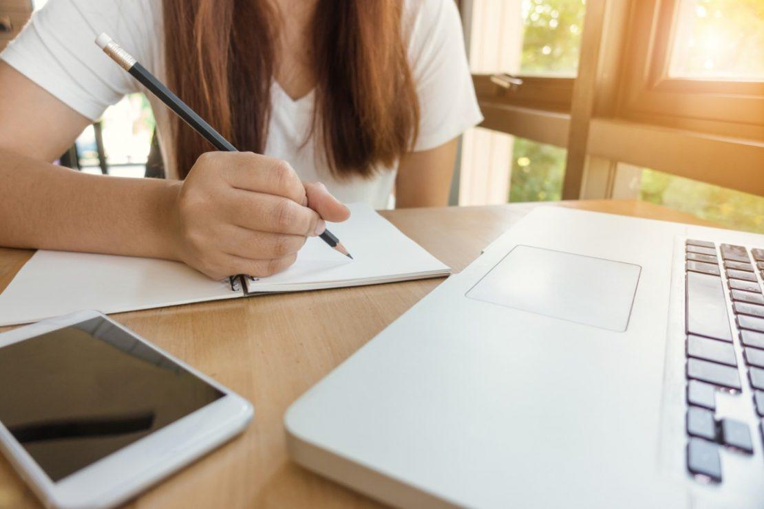 Студент сидит за столом с лэптопом и телефоном и составляет конспекты для предстоящих экзаменов.